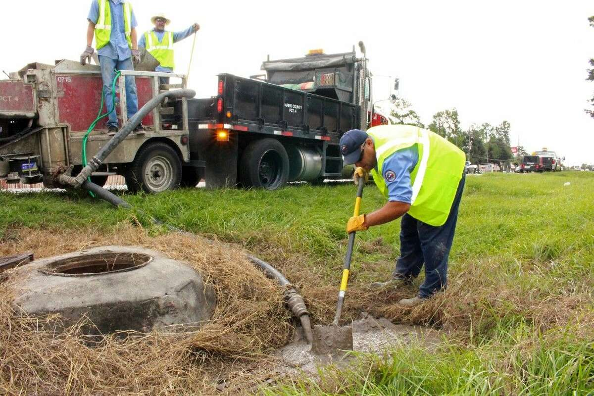 Robert Nave, a Road & Bridge staff member, spreads a cement mixture over a sinkhole caused by a leaking storm drain pipe.