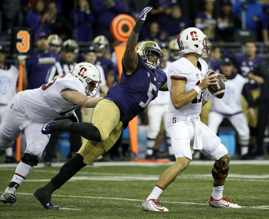 Washington's Joe Mathis sacks Stanford quarterback Ryan Burns — one of eight Huskies sacks on Friday night. Photo: Ted S. Warren, Associated Press