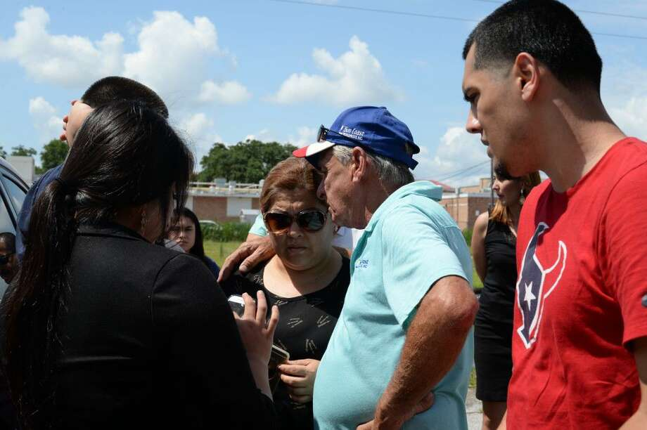 Tim MiIler (left), of Texas Equusearch, with members of the victim's family on Tuesday morning.