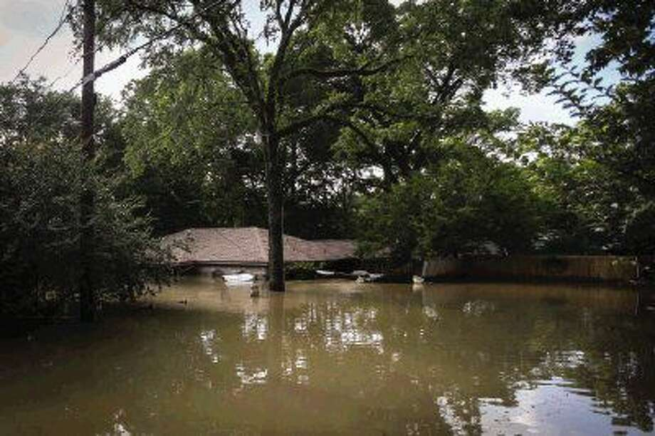 The home of 20-year residents Derick and Mary Dickman is pictured flooded with up to six feet of water on Saturday, May 28, 2016, on Rustling Pines Street in the Timber Ridge - Timber Lakes subdivision. Photo: Michael Minasi