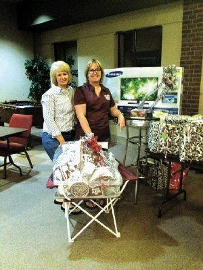 Gayle Keller and Geralyn Sullivan, KH Aggie Mom, banquet chairpersons, showing some of the auction items for the Nov. 12 fundraiser.