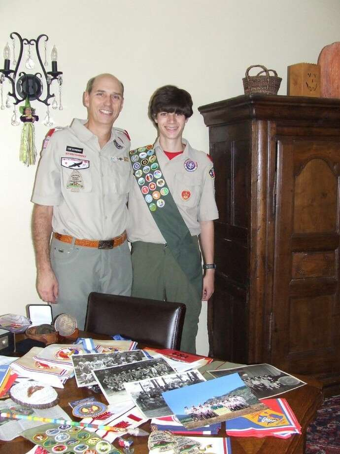Chip Schneider, left, and his son, Sam, stand in front of some of the Boy Scout memorabilia collected over the years.