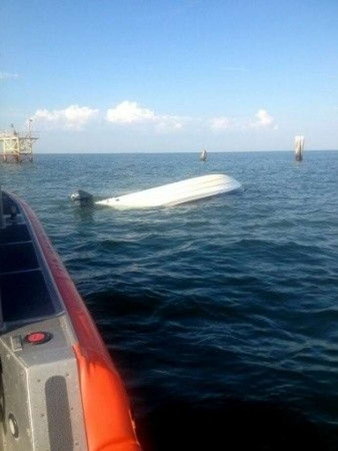 A capsized boat floats in Galveston Bay after Coast Guard boat crews from Station Galveston rescued two people sitting on the hull. USCG photo.