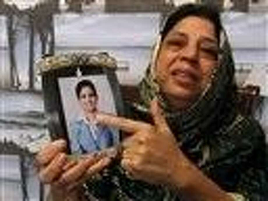 Pakistani mother, Sarwari Begum, shows a picture of her daughter, Bushra Khalique, 27, who is reportedly missing after a crush during the Hajj pilgrimage in Saudi Arabia, Saturday in Karachi, Pakistan. Photo: Fareed Khan