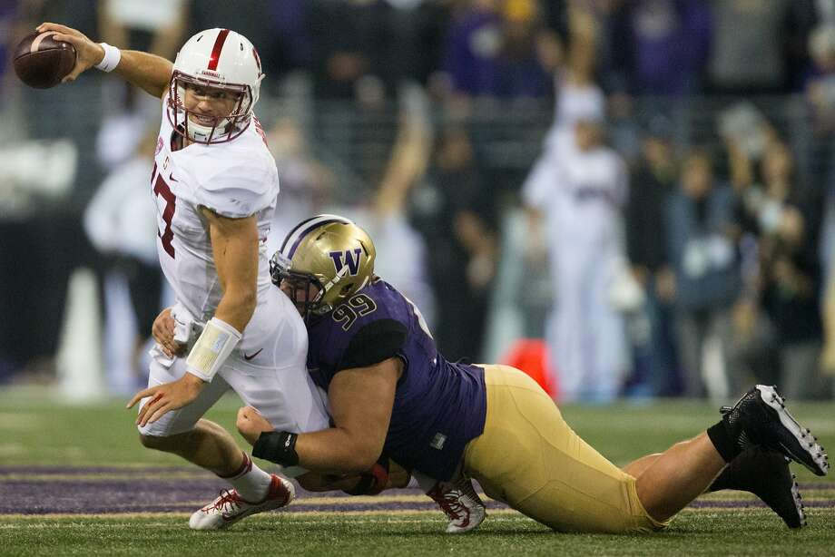 Stanford quarterback Ryan Burns is stacked by Washington defensive lineman Greg Gaines at Husky Stadium, Friday, Sept. 30, 2016.  (GRANT HINDSLEY, seattlepi.com) Photo: GRANT HINDSLEY, SEATTLEPI.COM
