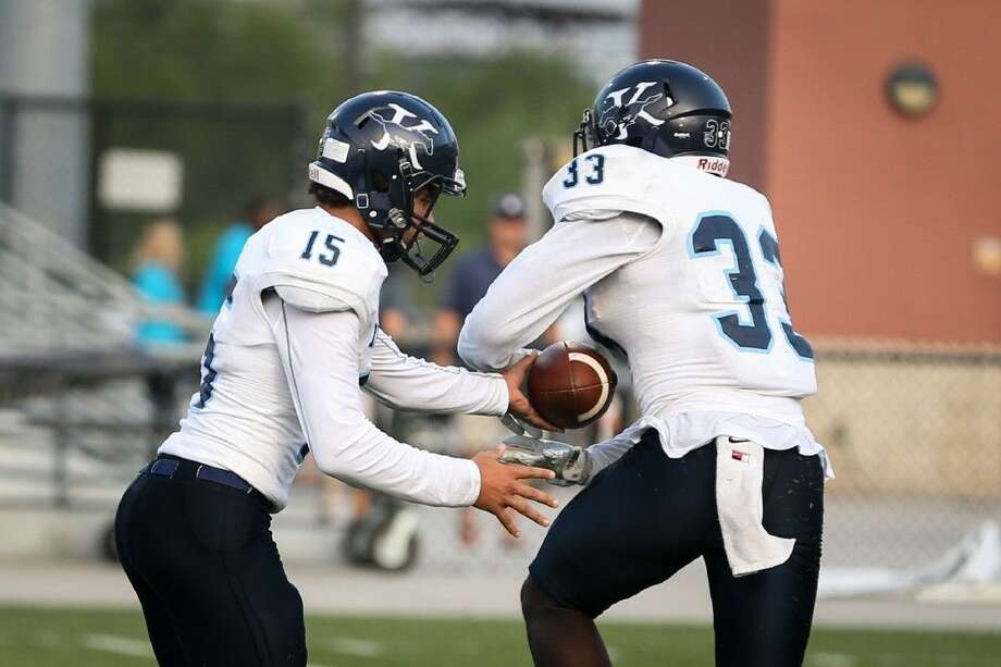 Kingwood's TJ West (15) hands the ball off to Sewo Olonilua (33) during the high school football game against Oak Ridge Saturday at Woodforest Stadium. To view more photos from the game, go to HCNPics.com. Photo: Michael Minasi