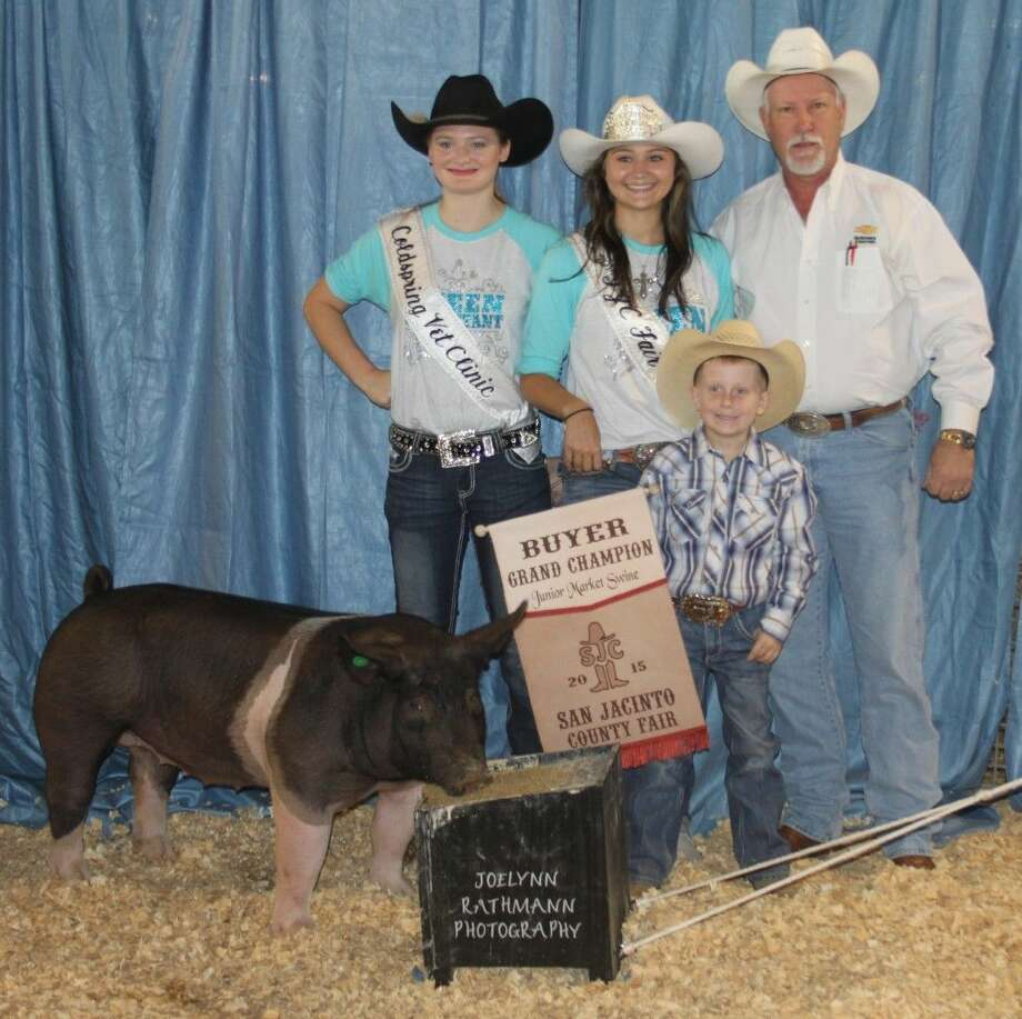 The Grand Champion Jr. Swine, raised by Cutter Hues (front), was sold to Martin Chevrolet Buick GMC for $1,000. Ken Syphrett (right) represented the dealership and standing with him are Rodeo Queen Savannah Spivey (middle) and 2015 Rodeo Queen contestant Skylar Sims. Photo: Jacob McAdams