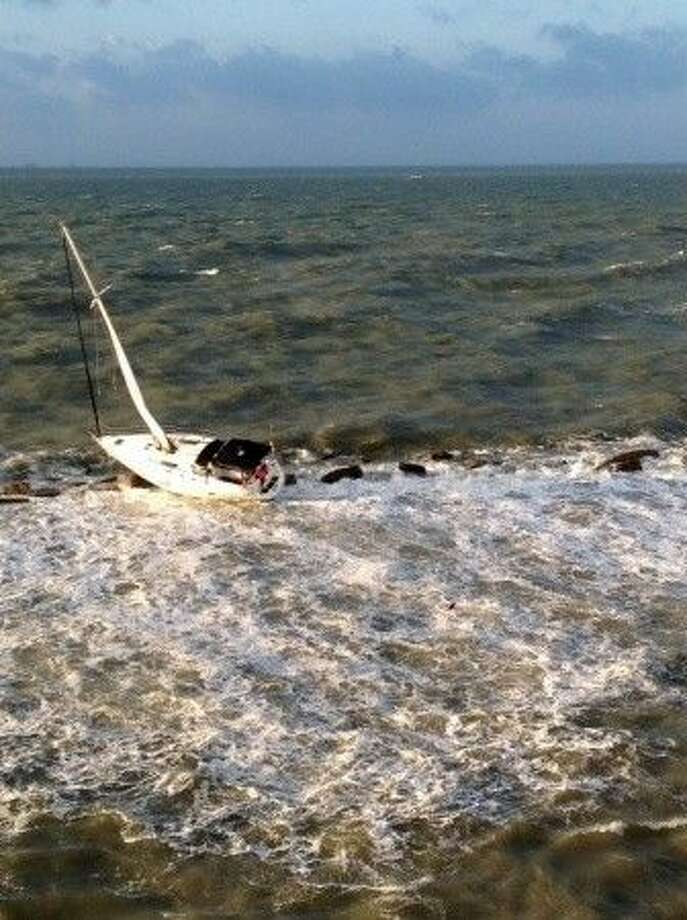 The sailboat French Kiss is battered on the Galveston south jetty after Coast Guard Station Galveston and Air Station Houston crews respond Monday, Oct. 13, 2014. The aircrew hoisted the two men to safety and one man was treated for minor injures. (U.S. Coast Guard photo by Air Station Houston).