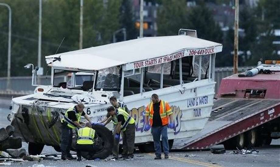 """Seattle Police officers photograph the front tire and wheel of a """"Ride the Ducks"""" tourist vehicle before the bus is loaded onto a flatbed tow truck Thursday after it was involved in a fatal crash with a charter passenger bus earlier in the day in Seattle. Photo: Ted S. Warren"""
