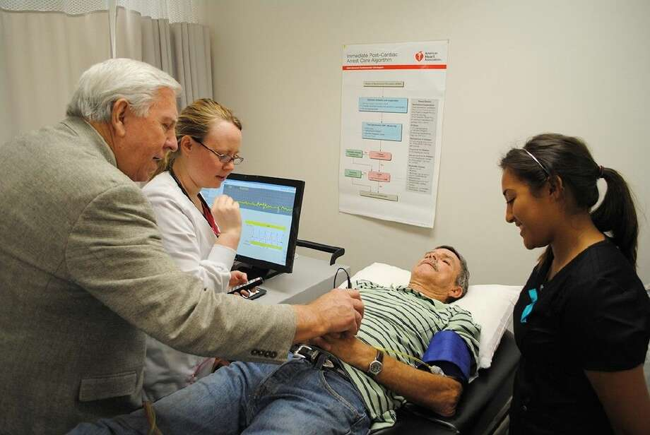 Vasculab president Norman Middleton, left, shows ACC students Chelsea Ziegler, second from left and Alyssa R. Garcia, right, how to use a new cardiovascular scanning technology with patient Ronnie Weaver during the ACC Fall Fitness Fair in 2013.