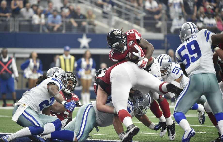 Atlanta Falcons running back Devonta Freeman scores during the first half of an NFL football game on Sunday in Arlington.
