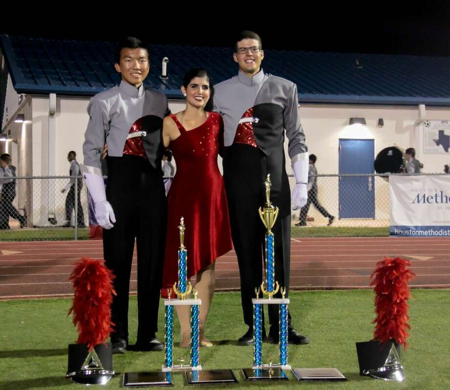 Drum Majors Mauricio Mondragon and Willy Xu and Angel colonel Jeslian DiCesare with the awards won at contest.