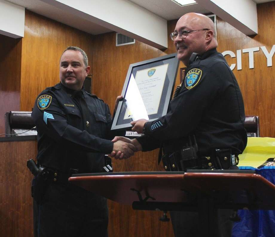 Chief Grigg presents Ian Sawtell with a framed certificate.