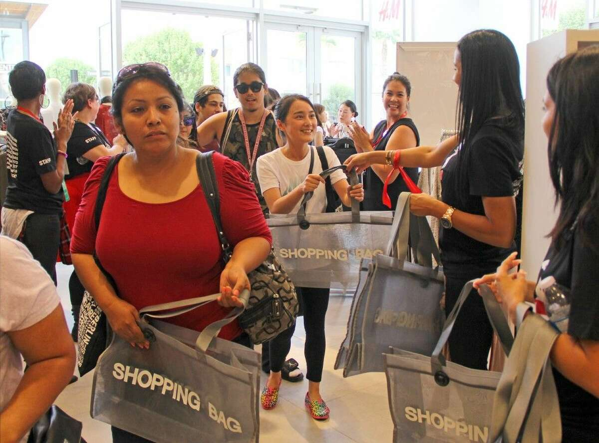 H&M associates cheer and hand out shopping bags to their new customers.