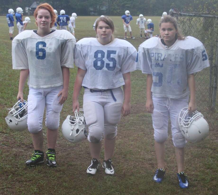 Amber Hauke (left), Kailey LaGarce (middle) and Sky Rushing put on their game faces as they prepare to practice at Shepherd Middle School alongside the boys in the rain on Monday, Sept. 28. Photo: Jacob McAdams