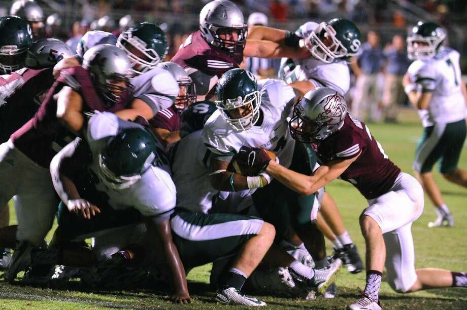 WIth a pile of his teammates, as well as Magnolia defenders, all surging forward, Stratford sophomore running back Chaise Ellis pushes his way into the end zone for a touchdown Friday night in the Spartans' 44-21 win over Magnolia at Magnolia ISD Stadium. Photo: Tony Gaines