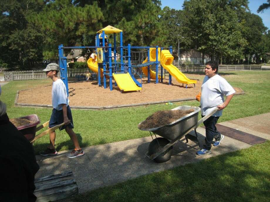 Kingwood Park Air Force JROTC members cart mulch to one of the playgrounds at Kingwood Park High School Saturday, Sept. 26, 2015.