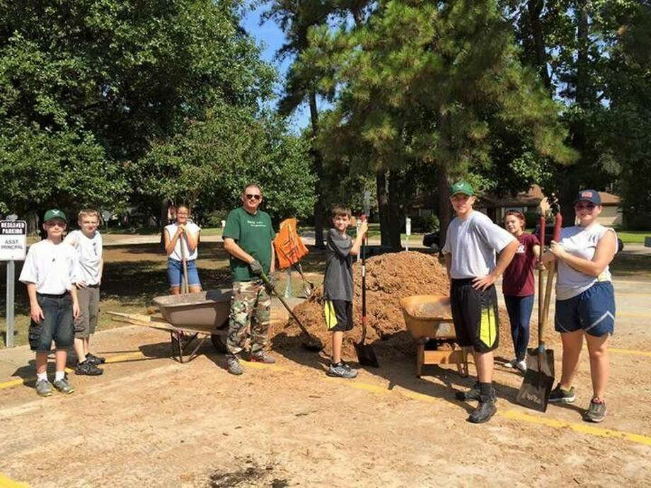 Armed with shovels and wheelbarrows, members of Kingwood Park High School's Air Force JROTC filled in the playgrounds and garden areas with cushion material at Woodland Hills Elementary with the help of supplies from Warren's Gardens.