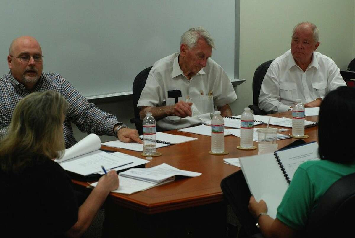 Still busy and working at 76 years old, John Hebert, at center, sits on the board of the Liberty County Foreign-Trade Zone, No. 171. Shown here at their last meeting, Trey Boring of IMS Worldwide, Inc., at left, described to the Liberty County Foreign Trade Zone board his firm's report at their annual meeting Thursday, Oct. 16. The other board members pictured are Bill Sjolander, seated on the right, and in the foreground are Kelly McDonald, the City of Cleveland's city manager, and Naomi Harrington, the City of Liberty's director of finance.
