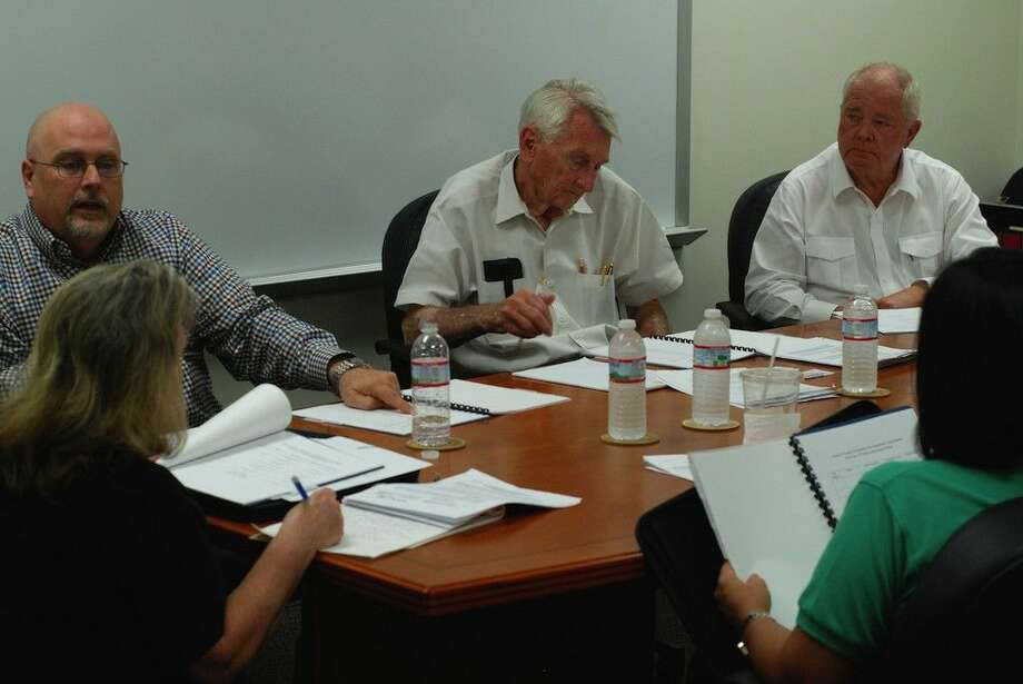 Still busy and working at 76 years old, John Hebert, at center, sits on the board of the Liberty County Foreign-Trade Zone, No. 171. Shown here at their last meeting, Trey Boring of IMS Worldwide, Inc., at left, described to the Liberty County Foreign Trade Zone board his firm's report at their annual meeting Thursday, Oct. 16. The other board members pictured are Bill Sjolander, seated on the right, and in the foreground are Kelly McDonald, the City of Cleveland's city manager, and Naomi Harrington, the City of Liberty's director of finance. Photo: Casey Stinnett