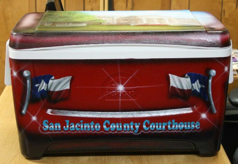 """The cooler for the Toyz for Kidz raffle sits in the San Jacinto County Judge's office. The front of the hand painted cooler depicts two Texas flags with the words """"San Jacinto County Courthouse"""" written on the bottom. The lid of the cooler has a painting of the courthouse itself. Photo: Jacob McAdams"""