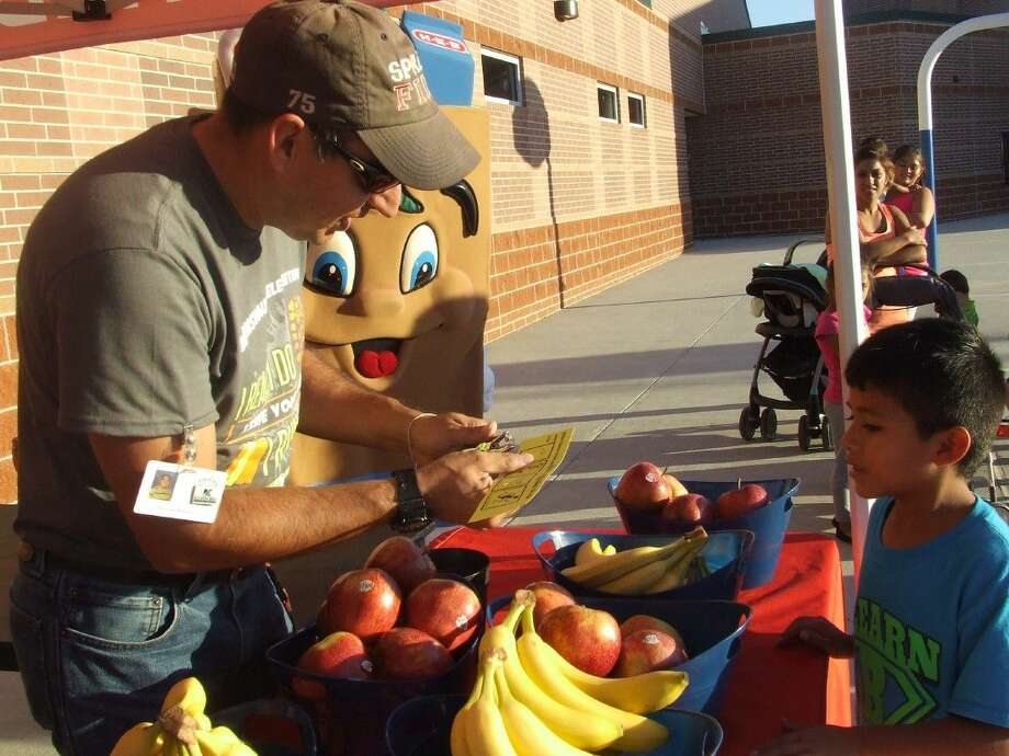 A first-grader at Bernshausen Elementary School waits to receive some fresh fruit after winning a round in the fruit walk sponsored by HEB during the Glow Power Family Run/Walk event on Friday, Oct. 17.