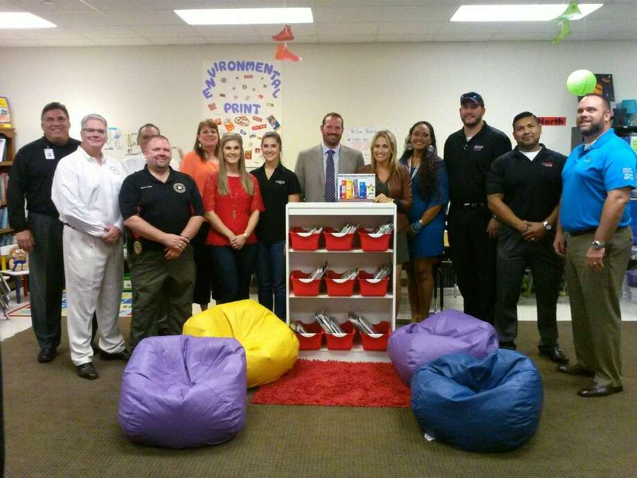 Funding for the Literacy Academy Classroom Library grant came from donations from The Signorelli Company, East Montgomery County Improvement District, Texan Drive and Joslin Construction. Donors pose by a classroom library at Oakley Elementary School.