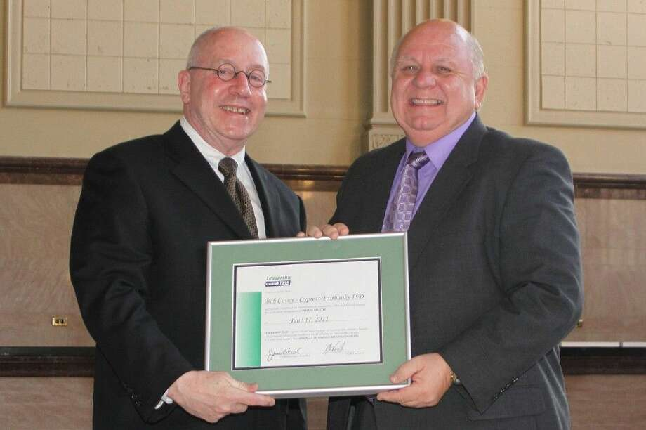 CFISD Board member Bob Covey accepts a Leadership TASB certificate from TASB representative William Nemir following a 2011 Leadership TASB training session. Photo: Submitted Photo