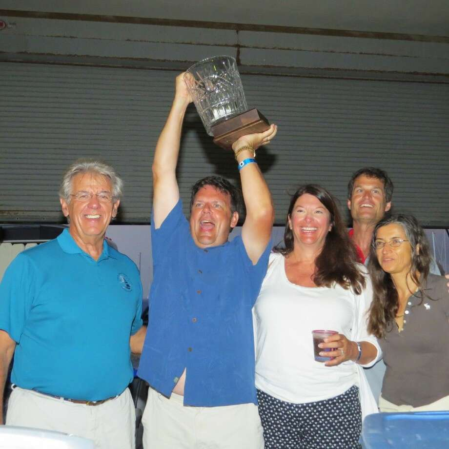 """Mayor's Trophy: First Multihull to finish - Bo Kersey and crew on """"Abandoned Asset"""" along with Harvest Moon Regatta Chairman Jack Seitzinger (far left)."""