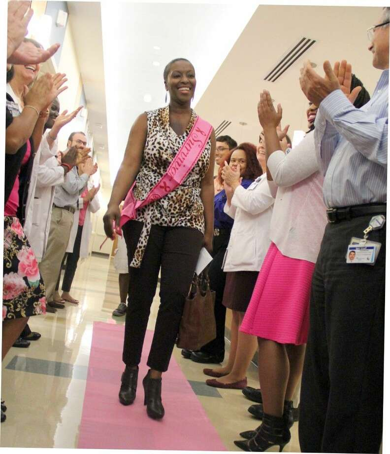 Doctors, nurses and staff members at CHI St. Luke's Health cheer Pearland-resident and breast cancer survivor Yvonne Dubra on finishing her last radiation treatment. Photo: Kristi Nix