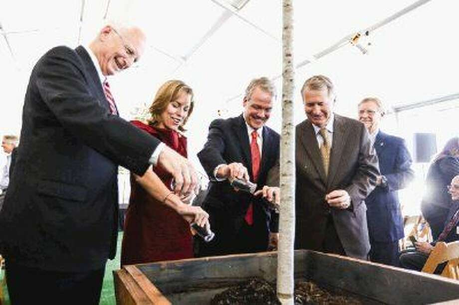 From left to right: Ewing Werlein Jr., Chair of Houston Methodist Board of Directors, Debra Sukin, Regional Senior Vice President of Houston Methodist, Marc Boom, President and CEO of Houston Methodist, and Ed Robb, Senior Pastor at The Woodlands United Methodist Church, pour soil around a tree during the Houston Methodist The Woodlands Hospital groundbreaking ceremony on Tuesday, Oct. 21, 2014, off of I-45 North in The Woodlands.