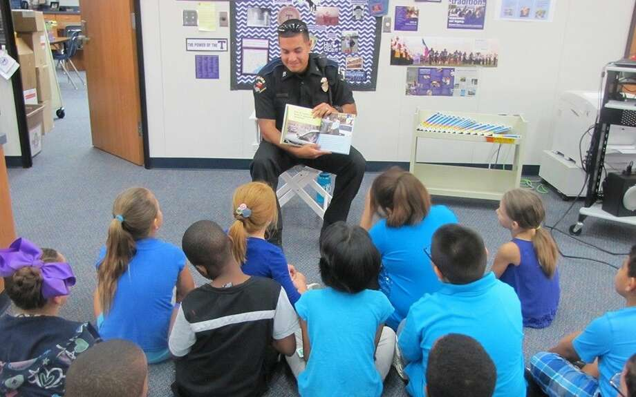 CFISD police officer Michael Gonzalez reads to McFee Elementary School students in September. Gonzalez and other officers will greet the community at National Night Out on Oct. 6.