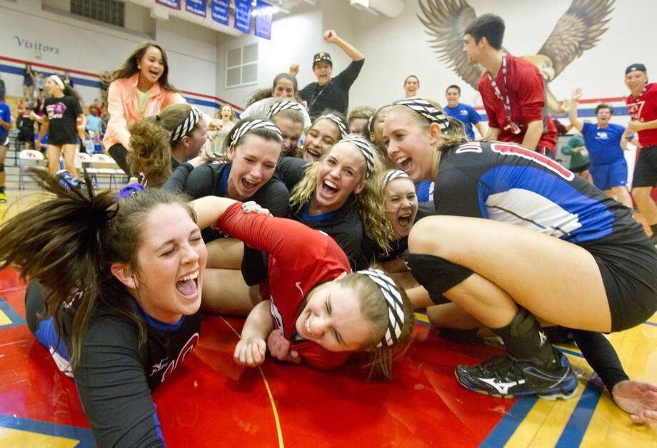Oak Ridge players celebrate after upsetting The Woodlands 3-1 during a high school volleyball game Tuesday. To view or purchase this photo and others like it, visit HCNpics.com. Photo: Jason Fochtman