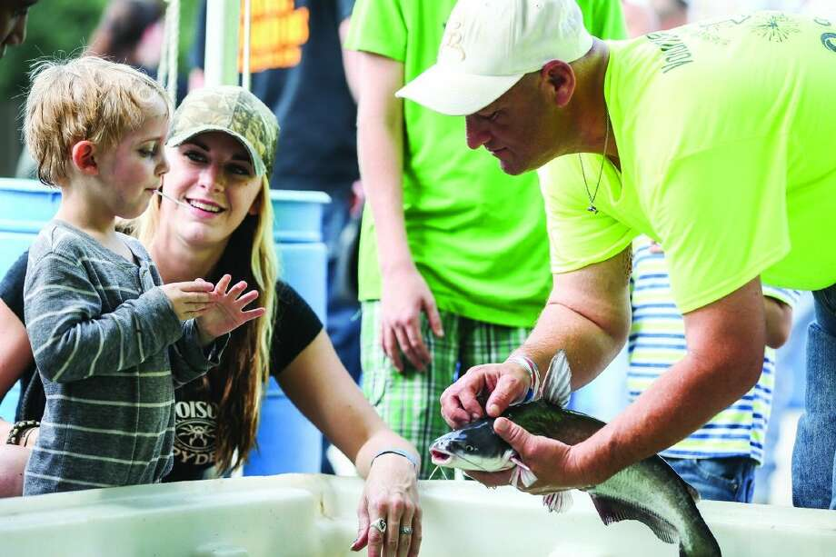Spring resident Stephanie Randall, center, watches her son, Ronnie Lamb, try to pet a live catfish held by Joel Luce of the Texas Fishing Forum, right, during the Conroe Cajun Catfish Festival in 2014. Photo: Photographer