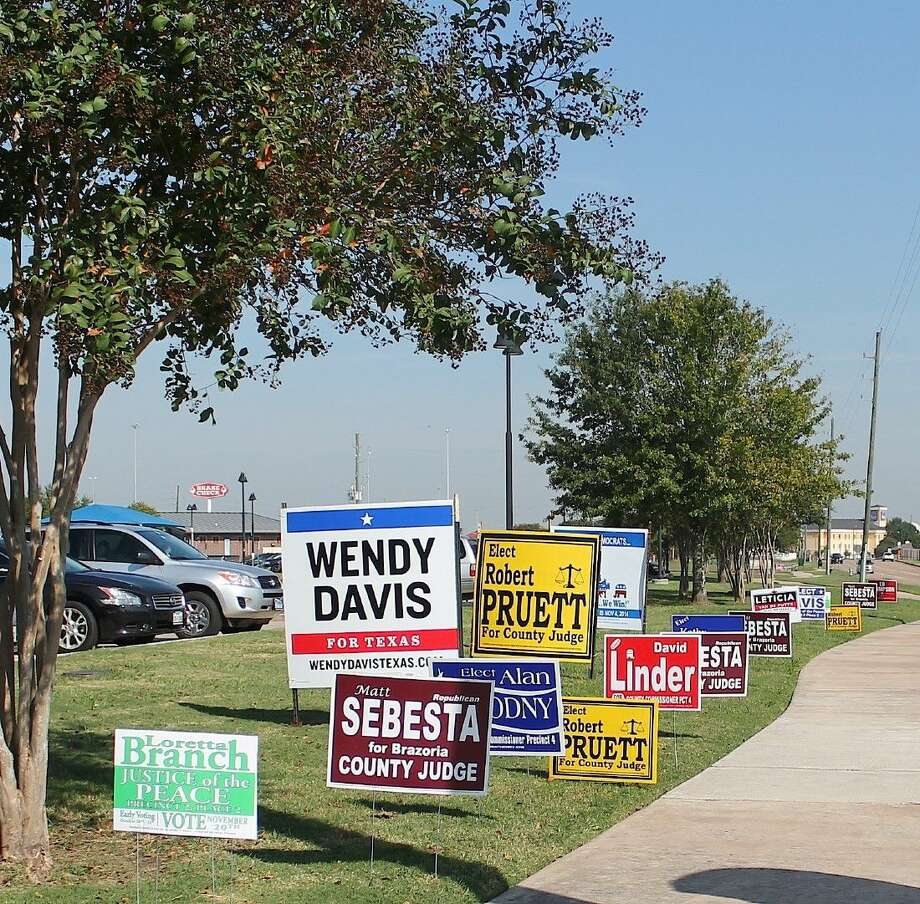 Political signs line the sidewalk leading to the Westside voting center in Pearland Monday. Photo: Stacey Glaesmann