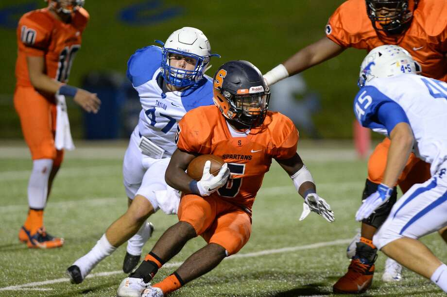 Seven Lakes' Brock Sturges looks for a hole as Taylor's Brantlund Goyens (47) and Nathan Saurage (45) close in Oct. 1 at Rhodes Stadium. Sturges rushed for 252 yards and four touchdowns to lead Seven Lakes to a 31-24 victory. Photo: Craig Moseley