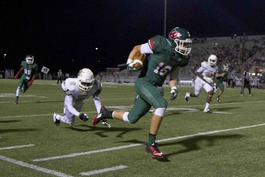 The Woodlands linebacker Zak Yhlecias returns an interception for a touchdown during a football game last Friday. To view or purchase this photo and others like it, visit HCNpics.com.