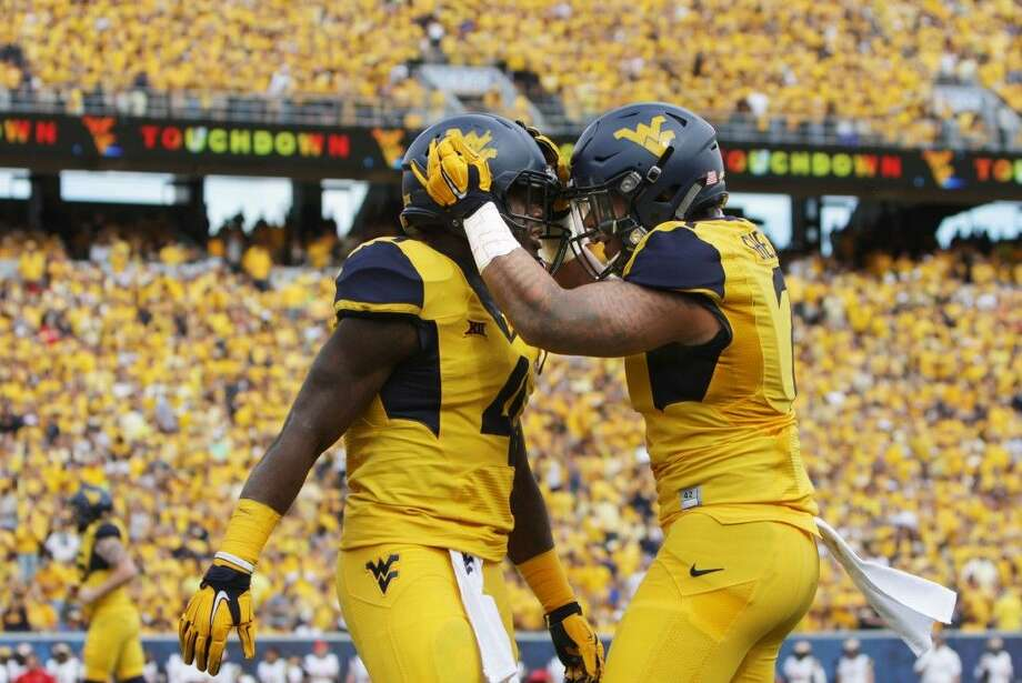West Virginia running back Wendell Smallwood (4) celebrates with his teammate West Virginia running back Rushel Shell (7) against Maryland last Saturday in Morgantown, W.Va. The Mountaineers (3-0) will play three of its first four conference games on the road, all are against ranked opponents, starting Saturday at No. 15 Oklahoma (3-0).