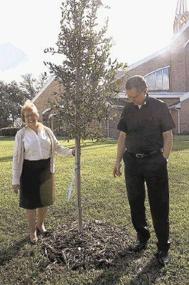 Bette Johnson and Rev. Wencil Pavlosky of Saint Paul the Apostle Catholic Church in Nassau Bay stand by the young live oak tree planted to honor Russian Cosmonaut Yuri Gagarin, the first man to travel into space, and his American counterpart and former senator John Glenn. The trees commemorate the 50th anniversay of man's first flights into space. Planting trees is one way to improve the community and provide year round enjoyment for people and habitat for birds and wildlife. Photo: Y.C. OROZCO