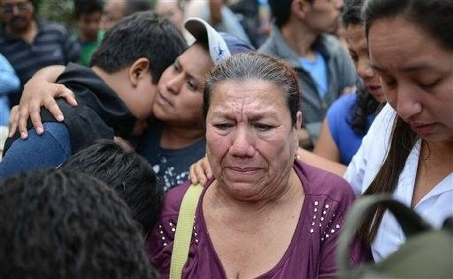 Friends and relatives wait for information outside a provisional morgue where the bodies recovered from the site of a landslide have been taken, in the suburb of Santa Catarina Pinula, about 10 miles east of Guatemala City, Friday. Photo: Oliver De Ros