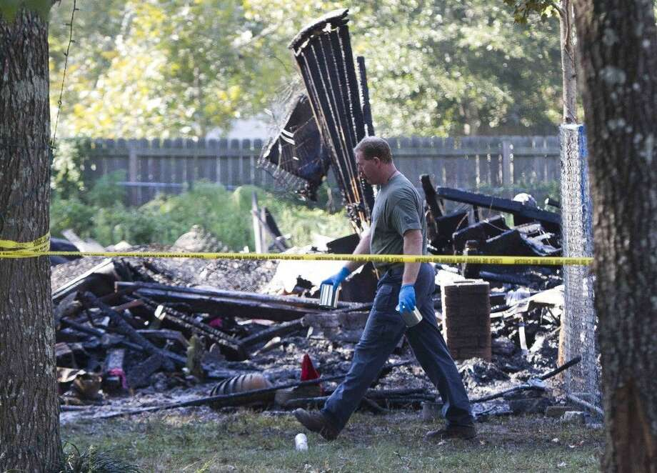 Investigators work the scene of a fatal fire in Porter Wednesday morning. Joseph Joucken, 57, was pronounced dead at the scene after trying to evacuate his family and the home collapsed while he was still inside. Photo: Jason Fochtman
