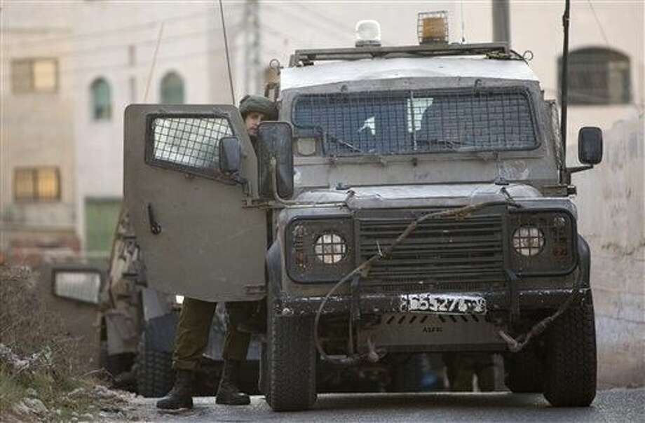 An Israeli soldier stands by a vehicle during an Israeli military raid in the West Bank city of Jenin, Sunday. Israeli troops shot and wounded at least 18 Palestinians in violence during an arrest raid in the Jenin refugee camp, a Palestinian hospital director said. Photo: Majdi Mohammed