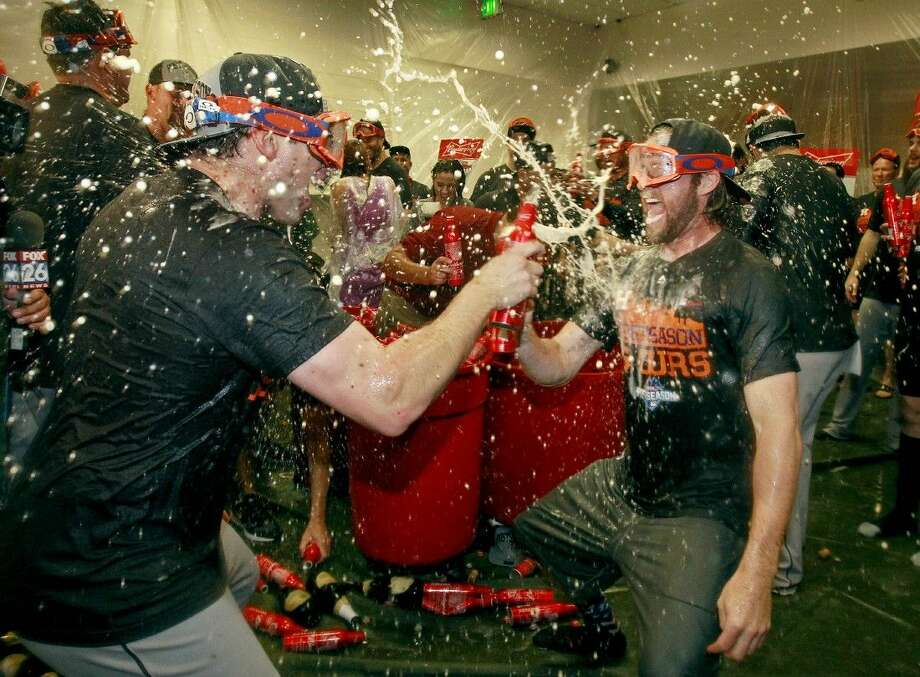 The Astros' Jed Lowrie, left, and Josh Fields celebrate their AL wild card playoff berth in Phoenix. The Astros face the New York Yankees in the AL wild-card game on Tuesday in New York.