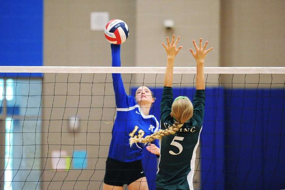 Klein's Brooke Laskoskie (No.13) spikes a shot past Spring for a kill. Photo: Photographer