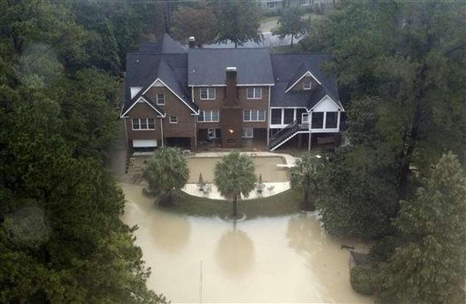 Floodwaters encroach on a large home in Columbia, S.C., Monday. After a week of steady rain, the showers tapered off Monday and an inundated South Carolina turned to surveying a road system shredded by historic flooding. Photo: Chuck Burton