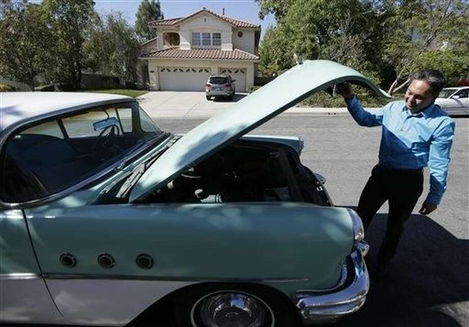 Ernie Rosales, 53, looks under the hood of his classic car in front of his home in Temecula, Calif. He returned to college in his 30s after he felt he had maxed out his potential income in California's aerospace industry with a pair of associate degrees. Photo: Chris Carlson