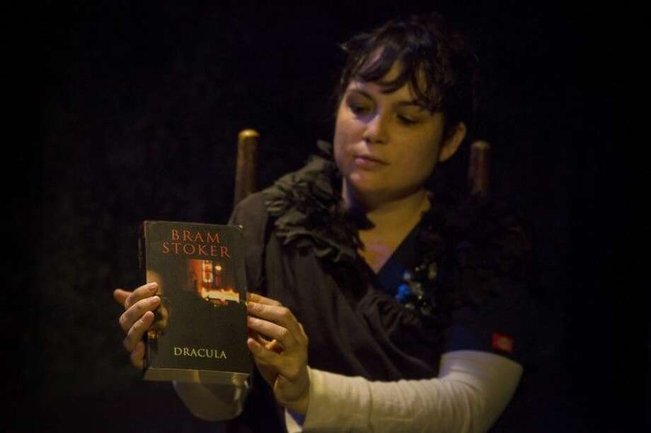 "Holding a copy of her ""beginning"" is the mad Renfield (Amey Richardson) as she appears in the Halloween thriller at Clear Creek Community Theatre, through November 2. Call 281-335-5228 for information or reservations."