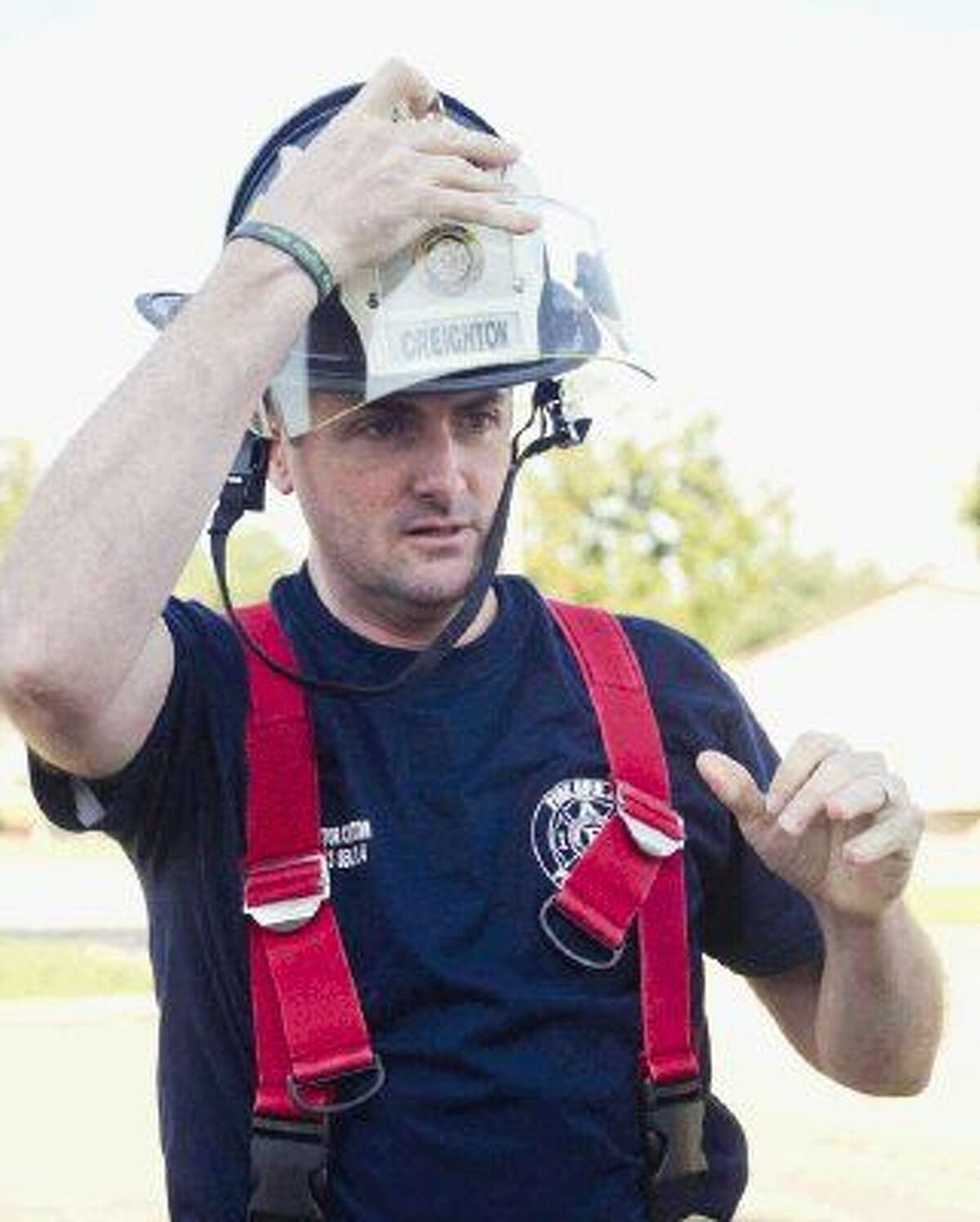 Texas Senator Brandon Creighton puts on a firefighter helmet during Fire Ops 101 training on Friday in Houston.