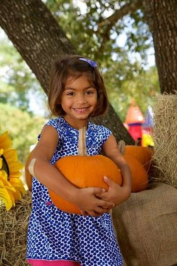 A girl picked out the perfect pumpkin for her photo at the 2014 Oak Ridge North Fall Festival. This year's event is from 10 a.m. to 2 p.m. Oct. 10 at Marilyn Edgar Park.