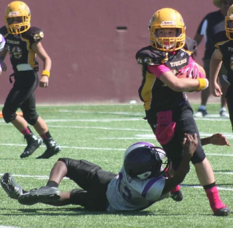 Deer Park Tiger Nicholas Lloyd protects the football as he tries to score from eight yards out during Saturday's game. Lloyd scored one play later to up the advantage to 13-0. Photo: Robert Avery